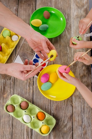 Easter. A happy family will paint eggs and get ready for Easter. Top view of the table with paints and eggs.