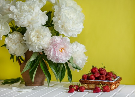 A large bouquet of peonies in a clay vase and a bowl of strawberries on a tree table. Romantic mood.