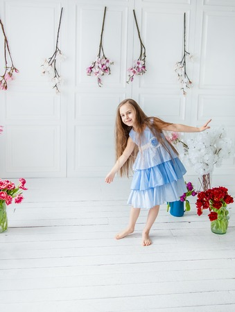 Portrait of a beautiful blue-eyed girl, a little girl among spring flowers in a bright room. Spring break, Mother's Day, Women's Day, Easter. Stok Fotoğraf