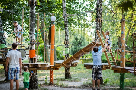 Portrait of cute little boy and girl walk on a rope bridge in an adventure rope park. Outdoor games.