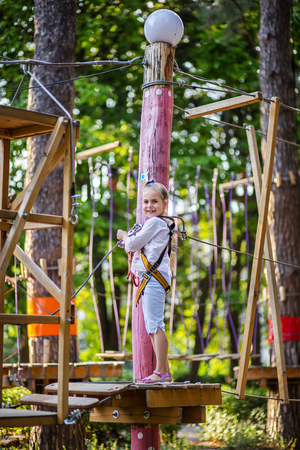 Portrait of a cute little girl who walks on a rope bridge in an adventure park rope. Outdoor games. Banque d'images