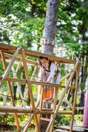 Portrait of a cute little girl who walks on a rope bridge in an adventure park rope. Outdoor games.