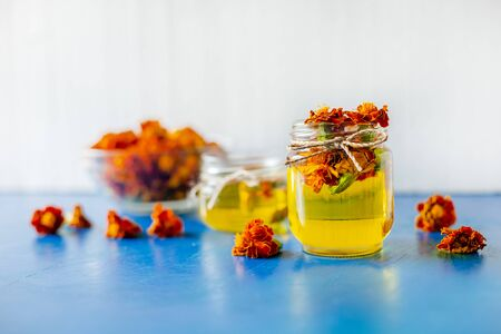 Processing of dried flowers marigolds. Bottle of Chornobrivtsi essential oil. Tages flower extract, tincture, infusion. Zdjęcie Seryjne