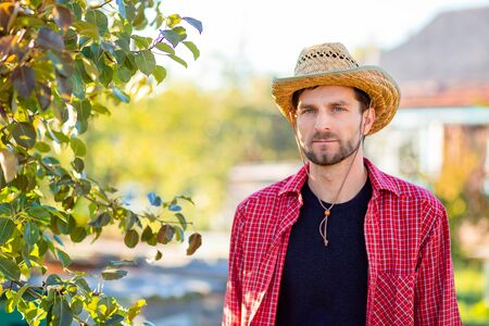 Handsome cowboy, portrait of a farmer in his garden. A man in a cowboy hat. Reklamní fotografie