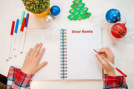 Dear Santa letter, Christmas card. A child holding a pen writes on a white sheet on a wooden background with New Year's decor. Childhood dreams about gifts. New Year concept. Stock Photo