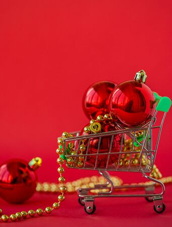 Gift Christmas balls in a miniature trolley and decorations on a red background. Christmas and New Year Sale, Christmas Online Store.