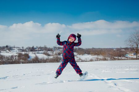 Cheerful girl jumping in the snow on a sunny winter day. Active games with snow. The winter vacation. Happy childhood