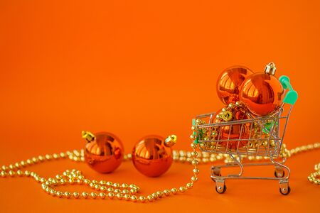 Gift Christmas balls in a miniature trolley and decorations on a Orange background. Christmas and New Year Sale, Christmas Online Store.