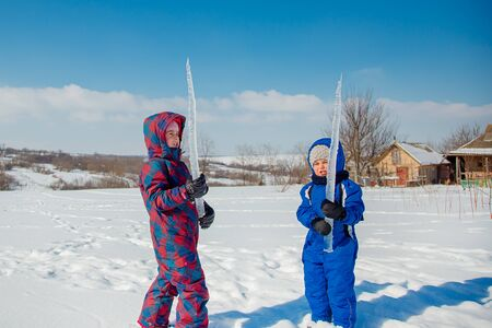 Happy brother and sister play on a winter walk, making snowballs in the park. Winter outdoor games. The winter vacation. Happy childhood.