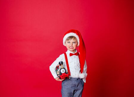 Merry Christmas. Cute cheerful little boy in Santa hat on red background. A happy childhood with dreams and gifts. Close-up of baby's open mouth, milk tooth fell out.