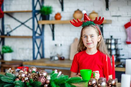 Good morning. A cute sleepy girl drinks tea at the kitchen table and hugs a teddy bear sitting in the kitchen. A time of miracles and fulfillment of desires. Merry Christmas.