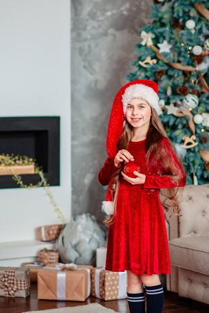 Portrait of a cheerful cute smiling girl in a santa hat with a red ball in hands, sitting near a decorated Christmas tree. Merry Christmas.