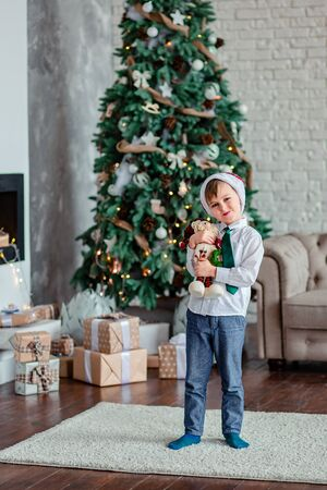Cute one boy unpacks gifts under the Christmas tree, sitting by the fireplace, on Christmas morning. Merry Christmas.