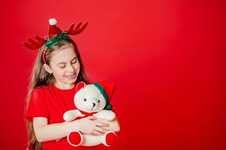 Portrait of a funny cheerful girl with a bandage of horns on her head hugging a teddy bear in Christmas pajamas isolated on a bright red background. The child points a hand, a place for text. Stock Photo