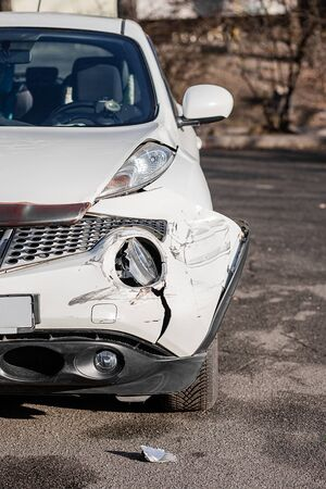 Inspection of the car after an accident on the road. Car accident or accident. The front wing and the right headlight are broken, damage and scratches on the bumper. Broken car parts or close-up. Imagens