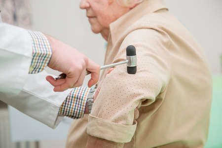 Orthopedic surgeon examining the knee reflex. The doctor checks the physiological reflex, the test hammer. Physician checking reflexes