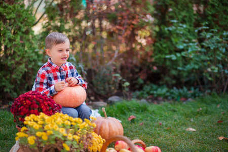 Merry painted pumpkin in the hands of a child. Halloween celebration. Small child is preparing for the holiday. 免版税图像 - 156752747