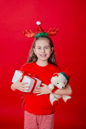 Portrait of a funny cheerful girl with a bandage of horns on her head hugging a teddy bear in Christmas pajamas isolated on a bright red background. The child points a hand, a place for text. 免版税图像 - 157538735