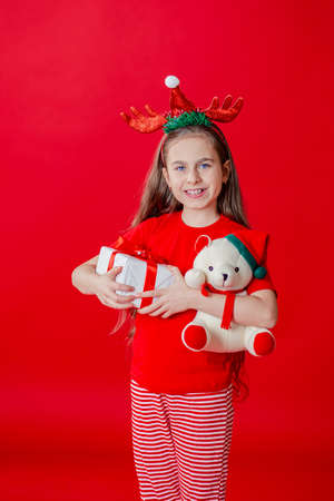 Portrait of a funny cheerful girl with a bandage of horns on her head hugging a teddy bear in Christmas pajamas isolated on a bright red background. The child points a hand, a place for text. 免版税图像 - 157538736