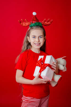 Portrait of a funny cheerful girl with a bandage of horns on her head hugging a teddy bear in Christmas pajamas isolated on a bright red background. The child points a hand, a place for text. 免版税图像 - 157538797