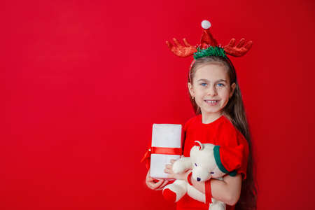 Portrait of a funny cheerful girl with a bandage of horns on her head hugging a teddy bear in Christmas pajamas isolated on a bright red background. The child points a hand, a place for text. 免版税图像 - 157538798