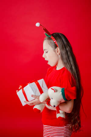 Portrait of a funny cheerful girl with a bandage of horns on her head hugging a teddy bear in Christmas pajamas isolated on a bright red background. The child points a hand, a place for text. 免版税图像 - 157538799