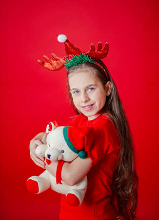 Portrait of a funny cheerful girl with a bandage of horns on her head hugging a teddy bear in Christmas pajamas isolated on a bright red background. The child points a hand, a place for text. 免版税图像 - 157538802