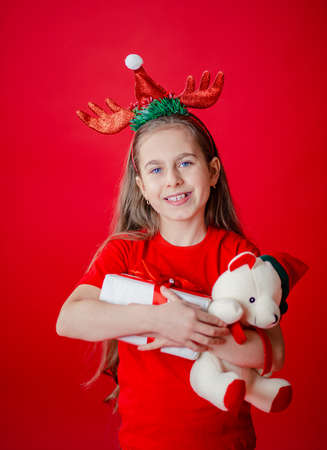 Portrait of a funny cheerful girl with a bandage of horns on her head hugging a teddy bear in Christmas pajamas isolated on a bright red background. The child points a hand, a place for text. 免版税图像 - 157538803