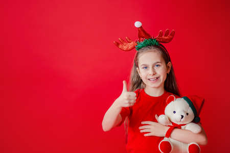 Portrait of a funny cheerful girl with a bandage of horns on her head hugging a teddy bear in Christmas pajamas isolated on a bright red background. The child points a hand, a place for text. 免版税图像
