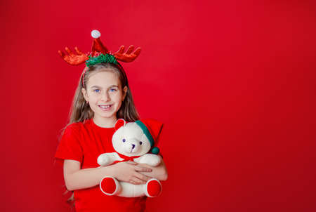 Portrait of a funny cheerful girl with a bandage of horns on her head hugging a teddy bear in Christmas pajamas isolated on a bright red background. The child points a hand, a place for text. 免版税图像 - 157538806