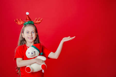 Portrait of a funny cheerful girl with a bandage of horns on her head hugging a teddy bear in Christmas pajamas isolated on a bright red background. The child points a hand, a place for text. 免版税图像 - 157538807