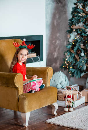 A cute girl in a Santa hat writes a letter to Santa near the Christmas tree. Happy childhood, a time for fulfilling desires. Merry Christmas. 免版税图像 - 157538935