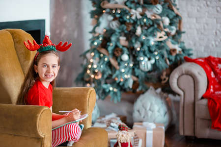 A cute girl in a Santa hat writes a letter to Santa near the Christmas tree. Happy childhood, a time for fulfilling desires. Merry Christmas. 免版税图像 - 157538936