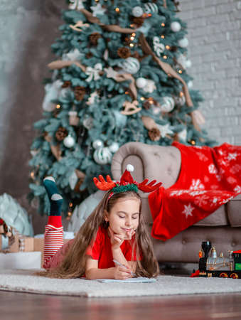 A cute girl in a Santa hat writes a letter to Santa near the Christmas tree. Happy childhood, a time for fulfilling desires. Merry Christmas. 免版税图像 - 157538938