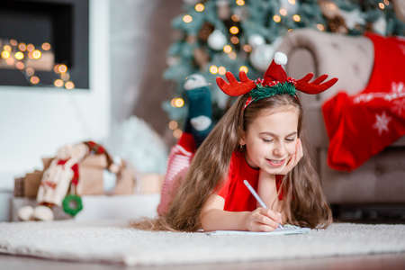 A cute girl in a Santa hat writes a letter to Santa near the Christmas tree. Happy childhood, a time for fulfilling desires. Merry Christmas. 免版税图像 - 157538942