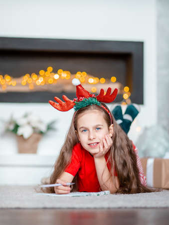 A cute girl in a Santa hat writes a letter to Santa near the Christmas tree. Happy childhood, a time for fulfilling desires. Merry Christmas. 免版税图像 - 157538943