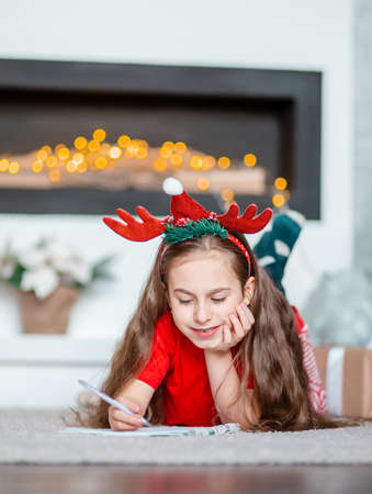 A cute girl in a Santa hat writes a letter to Santa near the Christmas tree. Happy childhood, a time for fulfilling desires. Merry Christmas. 免版税图像 - 157538944