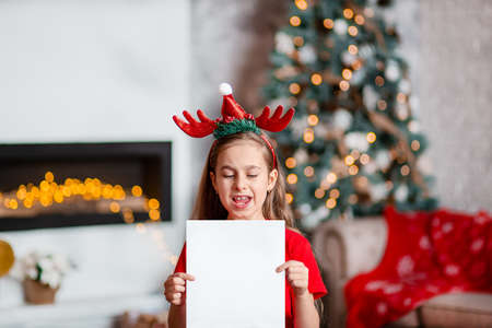 A cute girl in a Santa hat writes a letter to Santa near the Christmas tree. Happy childhood, a time for fulfilling desires. Merry Christmas.