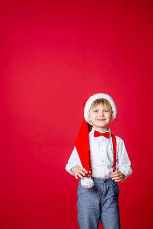 Merry Christmas. Cute cheerful little boy in Santa Claus hat on red background. A happy childhood with dreams and gifts. Close-up of baby's open mouth, milk tooth fell out. 免版税图像 - 157538950