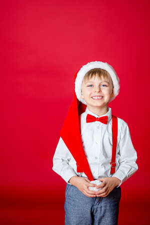 Merry Christmas. Cute cheerful little boy in Santa Claus hat on red background. A happy childhood with dreams and gifts. Close-up of baby's open mouth, milk tooth fell out. 免版税图像 - 157538948