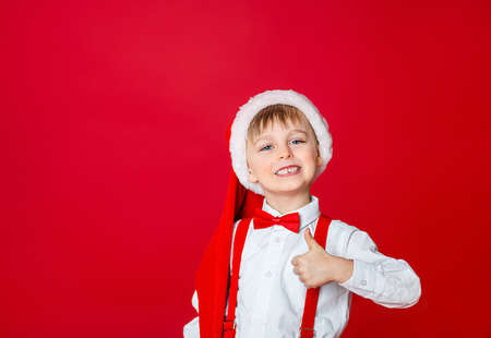 Merry Christmas. Cute cheerful little boy in Santa Claus hat on red background. A happy childhood with dreams and gifts. Close-up of baby's open mouth, milk tooth fell out. 免版税图像 - 157538949