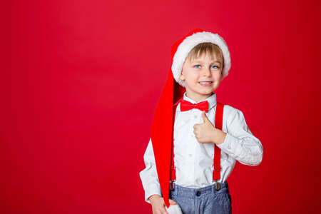 Merry Christmas. Cute cheerful little boy in Santa Claus hat on red background. A happy childhood with dreams and gifts. Close-up of baby's open mouth, milk tooth fell out.