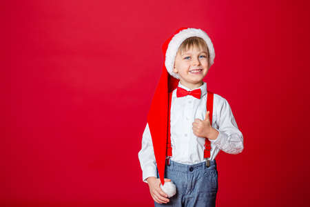 Merry Christmas. Cute cheerful little boy in Santa Claus hat on red background. A happy childhood with dreams and gifts. Close-up of baby's open mouth, milk tooth fell out. 免版税图像 - 157538953