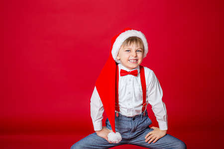 Merry Christmas. Cute cheerful cunning little boy in Santa Claus hat on red background. A happy childhood with dreams and gifts. Close-up of baby's open mouth, milk tooth fell out. 免版税图像