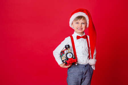 Merry Christmas. Cute cheerful cunning little boy in Santa Claus hat on red background. A happy childhood with dreams and gifts. Close-up of baby's open mouth, milk tooth fell out. 免版税图像 - 157539120