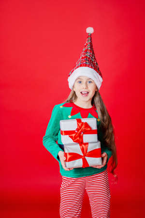 Merry Christmas, happy attractive girl with gifts in a costume of Santa Claus helper elf on a bright red bright color background. Portrait of a beautiful elven baby. Copy space. 免版税图像 - 157539125