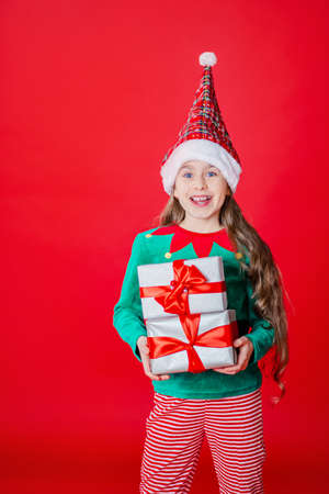 Merry Christmas, happy attractive girl with gifts in a costume of Santa Claus helper elf on a bright red bright color background. Portrait of a beautiful elven baby. Copy space. 免版税图像 - 157539126