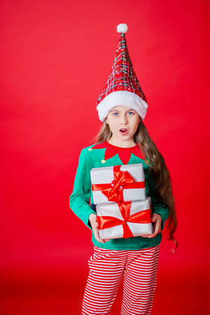 Merry Christmas, happy attractive girl with gifts in a costume of Santa Claus helper elf on a bright red bright color background. Portrait of a beautiful elven baby. Copy space.