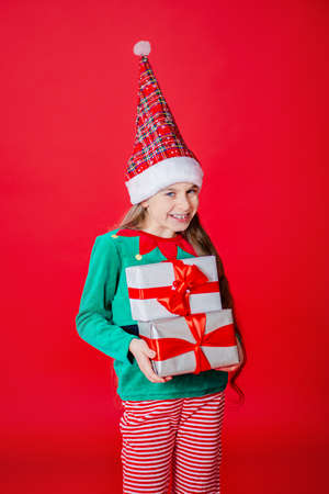 Merry Christmas, cunning happy attractive girl with gifts in a costume of Santa Claus helper elf on a bright red bright color background. Portrait of a beautiful elven baby. Copy space. 免版税图像 - 157539129