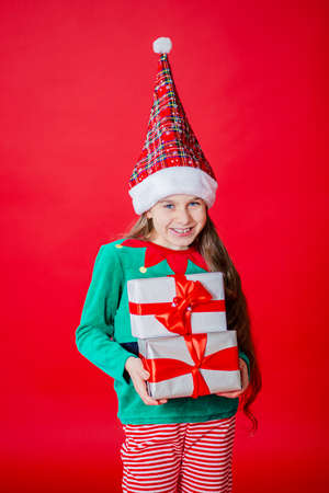Merry Christmas, cunning happy attractive girl with gifts in a costume of Santa Claus helper elf on a bright red bright color background. Portrait of a beautiful elven baby. Copy space.